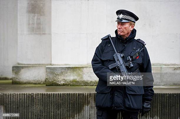 Armed British police officers stand on duty in central London on November 25 2015 Britain's Chancellor of the Exchequer George Osborne is set to...