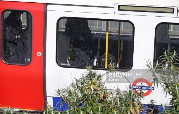 Armed British police officers walk through the carriage of a London underground tube carriage at Parsons Green underground tube station in west...