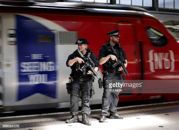 TOPSHOT Armed British Transport Police Specialist Operations officers patrol on the platform before boarding a Virgin train to Birmingham New Street...