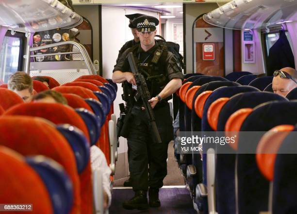 Armed British Transport Police Specialist Operations officers patrol on board a Virgin train to Birmingham New Street at Euston station in London For...