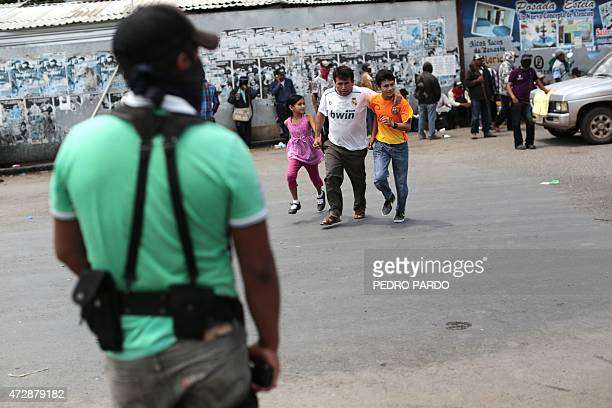 Armed civilians stand guard in Chilapa Guerrero State Mexico on May 10 2015 About 300 people armed with rifles sticks and machetes arrived on the eve...