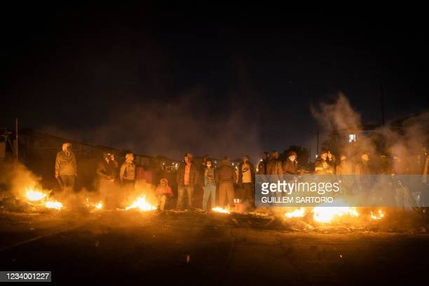 Armed community members gather around a fire to keep warm at a road block set up in Phoenix Township, North Durban, on July 15, 2021 to prevent...