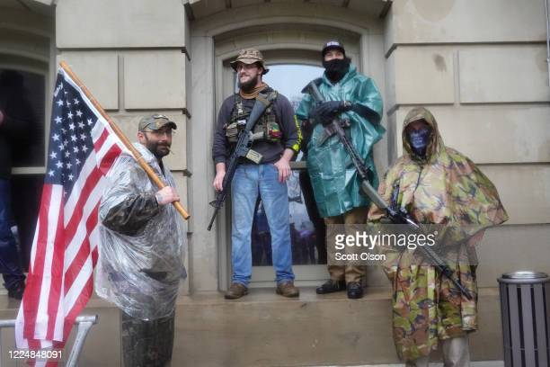 Armed demonstrators attend a rally in front of the Michigan state capital building to protest the governor's stayathome order on May 14 2020 in...