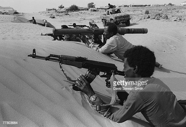 Armed fighters in Mogadishu resting their machine guns and rocket launchers on the sand dunes during the Somalian civil war, January 1992.