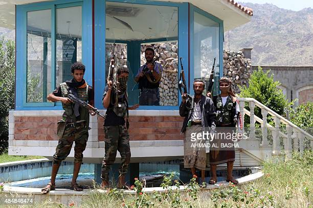 Armed fighters loyal to Yemen's exiled President Abedrabbo Mansour Hadi stand in the garden of a house of former president Ali Abdullah Saleh after...