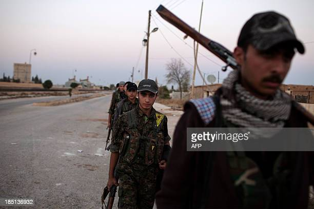 Armed fighters of the Committees for the Protection of the Kurdish People walk before taking position along the font line on October 16 2013 in the...