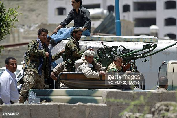 Armed fighters of the Shiite Huthi movement sit in a pickup truck mounted with a machinegun in southern Sanaa on April 21 in an area close to the...
