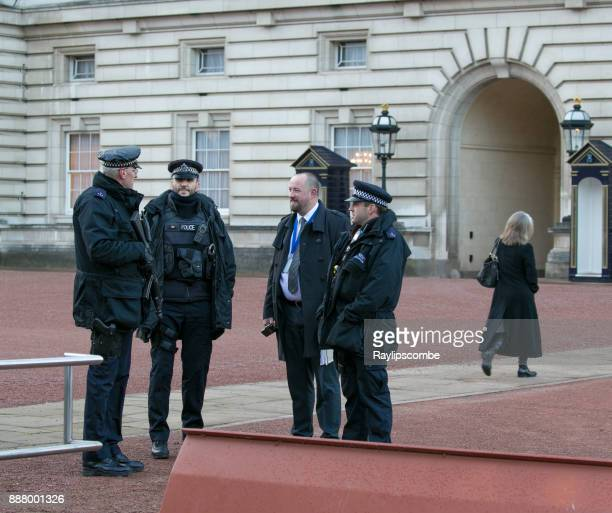 armed guards and security personnel talking outside buckingham palace as palace staff walk to work - royal navy stock pictures, royalty-free photos & images