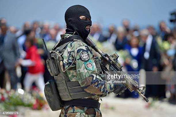 Armed guards patrol Marhaba beach during a visit by British Home Secretary Theresa May at the scene where 38 people were killed on Marhaba beach last...