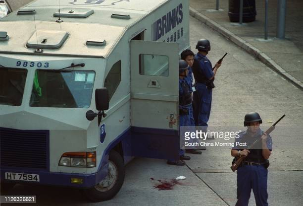 Armed guards secure a Brinks armoured car at Ying Fung Lane in Wong Tai Sin on 6 June 2002 Three knifewielding men escaped with $12 million in a...