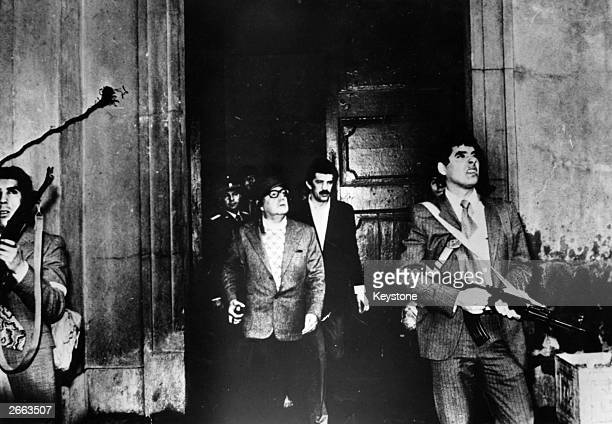 Armed guards watch out for attackers as Chilean president Salvador Allende leaves the Moneda Presidential Palace during the military coup in which he...