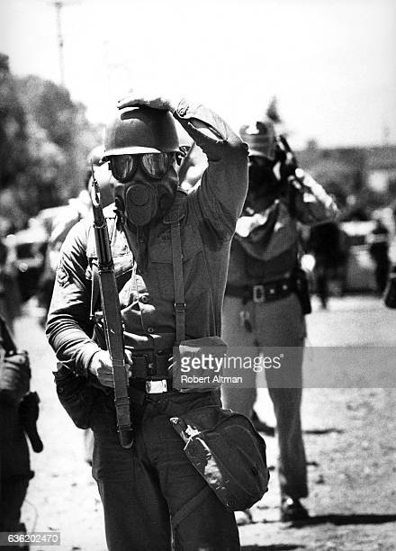 Armed guards wearing gas masks fire tear gas at protesters after the California Highway Patrol and Berkeley police officers destroyed trees flowers...