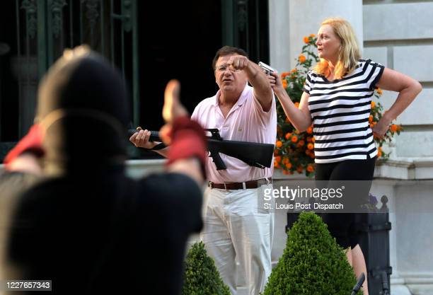 Armed homeowners Mark T. And Patricia N. McCloskey stand in front their house along Portland Place as they confront protesters marching to St. Louis...