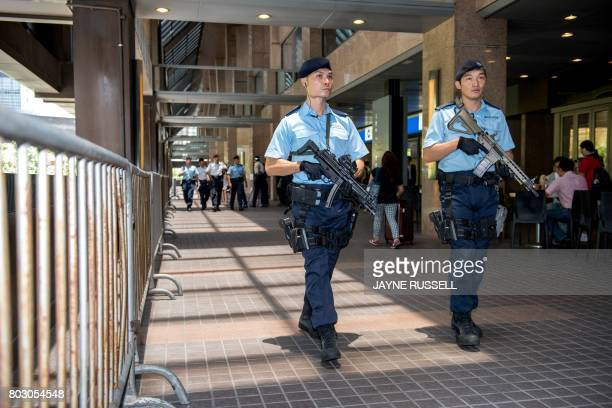 Armed Hong Kong police patrol the walkways overlooking the area where Chinese President Xi Jinping is staying in Hong Kong on June 29 as he visits to...