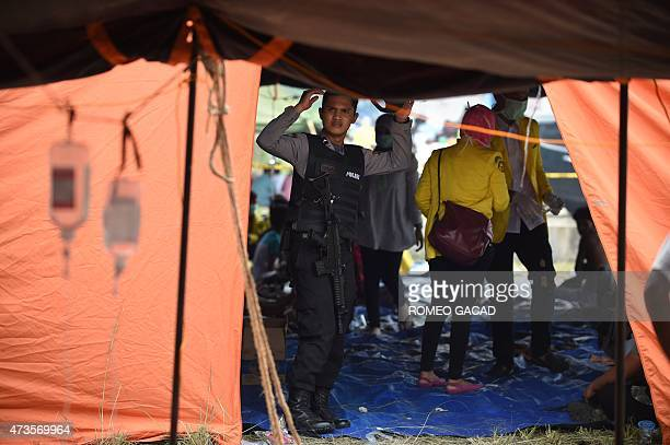 Armed Indonesian police accompany medical personnel attending to rescued Bangladeshi migrants with severe dehydration and wounds in the new...