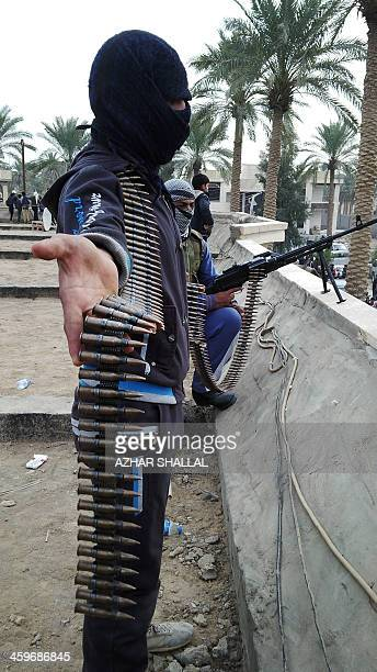 Armed Iraqi men stand guard as people gather to protest near the home of arrest Sunni Muslim MP Ahmed alAlwani in Ramadi west of Baghdad on December...