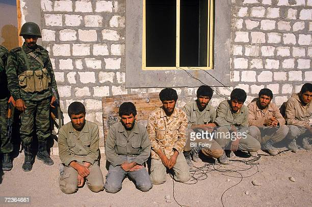 Armed Iraqi soldier stands guard by seven Iranian POW's at 7th Army headquarters