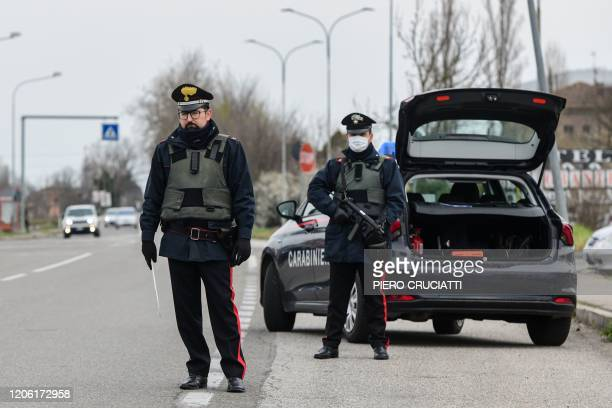 Armed Italian Carabinieri police officers hold a road check point at the border between the quarantined provinces of Modena and Bologna on March 9...