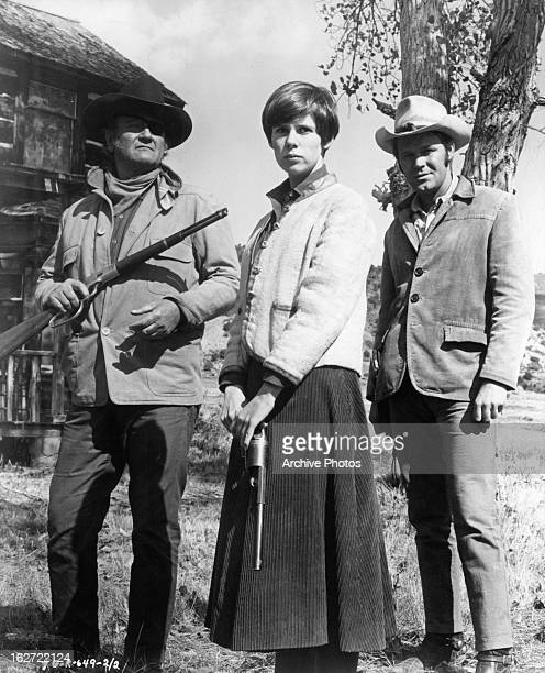 Armed John Wayne and Kim Darby standing next to Glen Campbell outside in a scene from the film 'True Grit' 1969