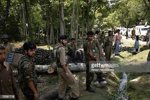 Armed Kashmiri police watch for a possible Islamic militant attack while a Kashmiri state government minister speaks to villagers on July 28 2005 in...