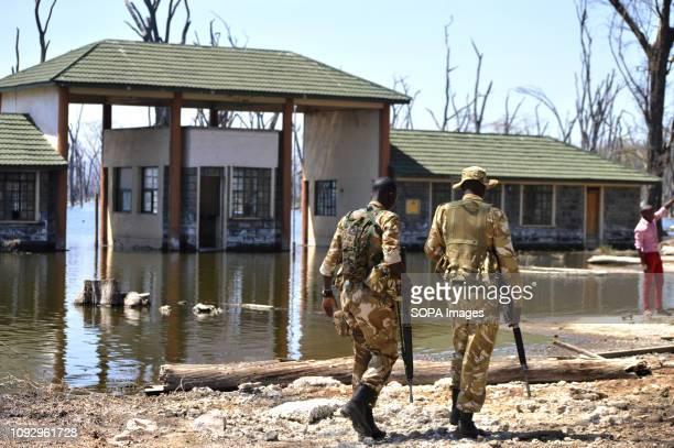 PARK NAKURU RIFTVALLEY KENYA Armed Kenya Wildlife Service game rangers seen walking past a submerged office buildings from the rising water levels in...