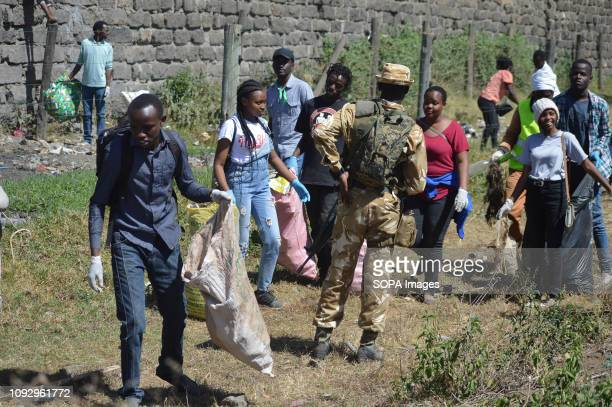 PARK NAKURU RIFTVALLEY KENYA Armed Kenya Wildlife Service game rangers seen watching over a group of students conducting a cleanup exercise during...