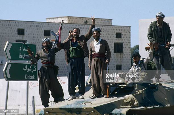 Armed Kurdish fighters stand on a tank raising their arms in victory.   Location: Salaheddine, Iraq.