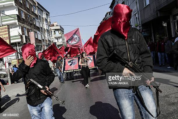 Armed left wing militans escort the coffins of victims who were killed at suicide bomb attack in Suruc as they arrive at Gazi Cemevi an Alevi...