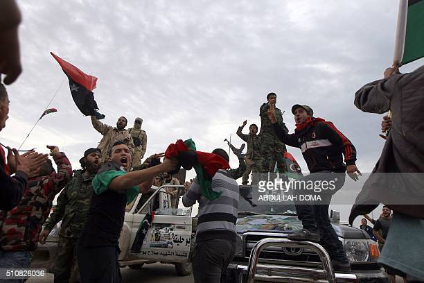 Armed Libyan men take part in a demonstration marking the fifth anniversary of the Libyan revolution which toppled strongman Moamer Kadhafi in the...
