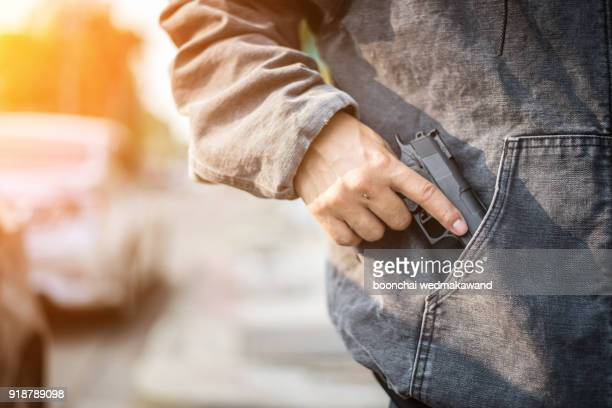 armed man (attacker) holds pistol in public place. many people on street. gun control concept. - ハイジャック ストックフォトと画像