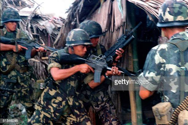 Armed marines carry out a house to house search in the southern part of Jolo island 23 October for the three Chinese kidnap victims from Hong Kong...