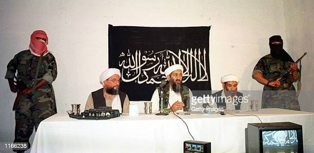 Armed masked men stand guard as suspected terrorist Osama bin-Laden and Ayman Al-Zawahiri address a news conference May 26, 1998 in Afghanistan. A...