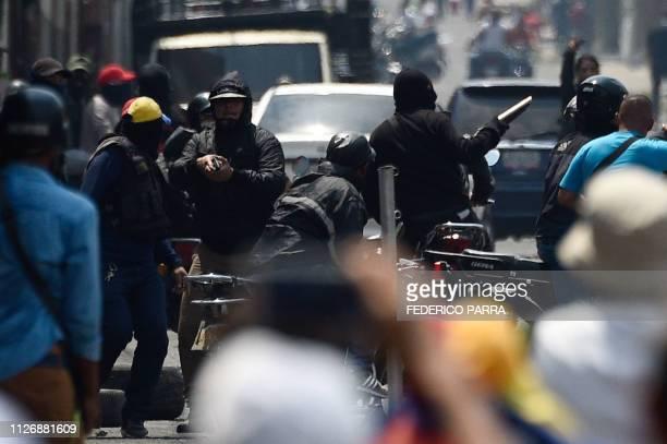 Armed members of a proMaduro militia attempt to disperse opposition demonstrators in San Antonio del Tachira Venezuela on February 23 2019...