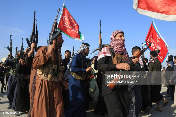 Armed members of Karbala clans lift their guns as they take to the streets in a show of force and to keep order amidst ongoing anti-government...