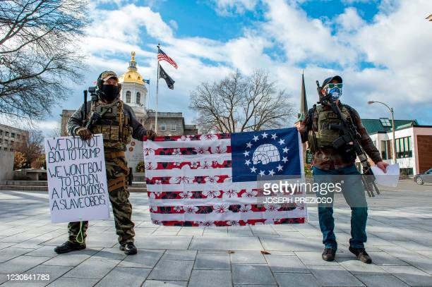 Armed members of the Boogaloo militia stand holding a flag in front of the State Capital in Concord, New Hampshire on January 17 during a nationwide...