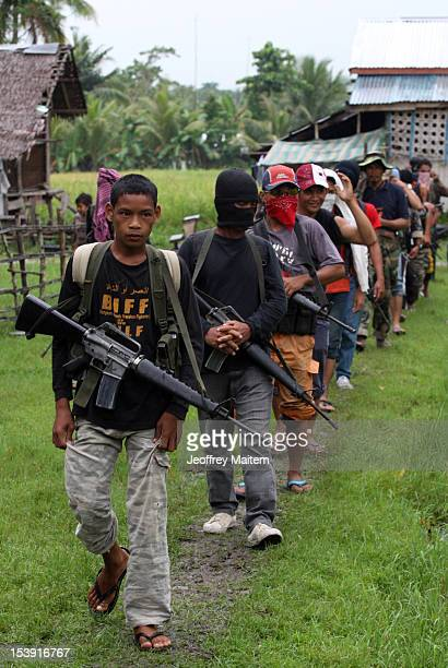 Armed members of the breakaway faction of the Moro Islamic Liberation Front walk through a village ahead of the signing of an agreement between their...