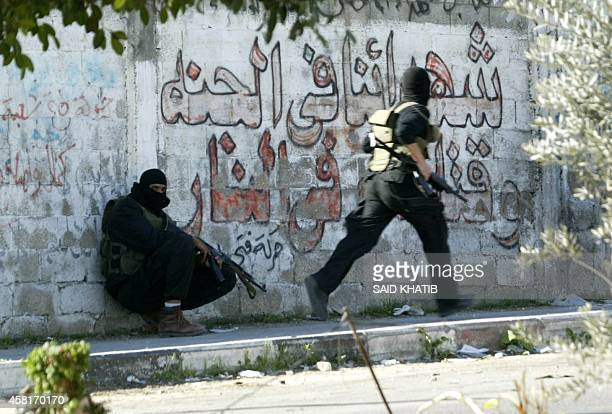 Armed members of the executive forces loyal to the ruling Hamas movement take cover on a street Gaza City 19 December 2006 Two Palestinians loyal to...