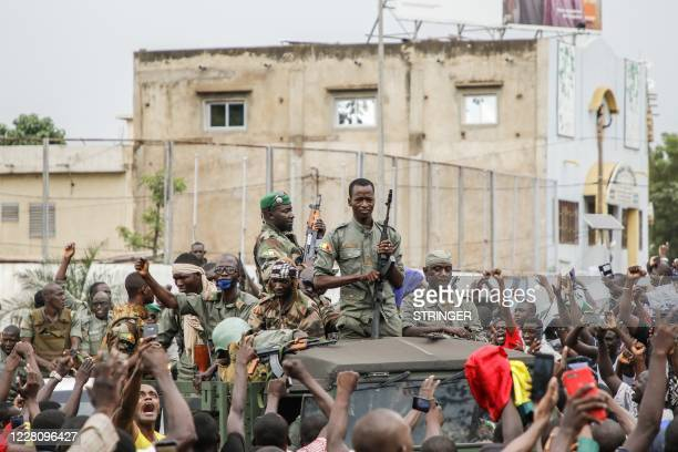 TOPSHOT Armed members of the FAMA are celebrated by the population as they parade at Independence Square in Bamako on August 18 after rebel troops...