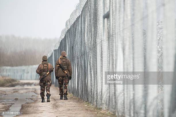 Armed members of the Hungarian military patrol by the razor wired topped security fence on the Hungarian-Serbian border near Roszke, Hungary, on...
