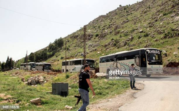 Armed members of the Lebanese General Security Directorate stand guard past buses evacuating Syrian refugees from the southern Lebanese village of...
