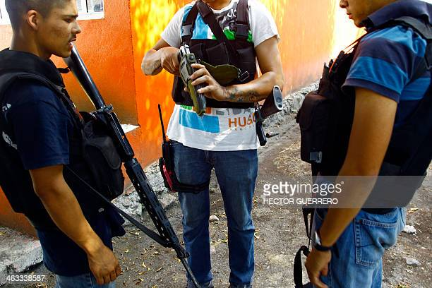 Armed members of the socalled selfdefence groups look at weapons seized to cartel members as they take control back from them of the community La...