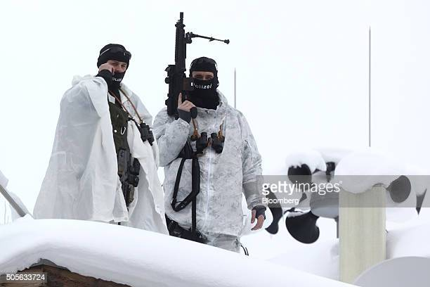 Armed members of the Swiss Police watch from the roof of the Hotel Davos ahead of the World Economic Forum in Davos Switzerland on Tuesday Jan 19...