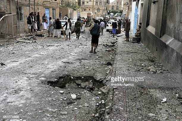 Armed men from Yemen's Houthi group gather at the scene after suicide car bombing attack outside the al Faid masjid in Nuqum region in Yemeni capital...