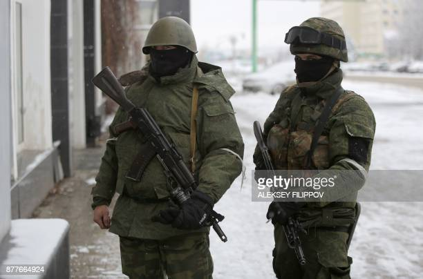 Armed men in military fatigues block access to government buildings in eastern Ukraine's rebelheld Lugansk on November 23 2017 The patrols began...