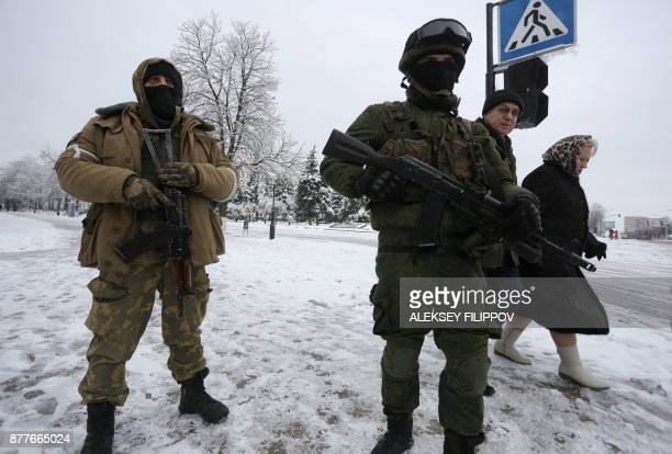 Armed men in military fatigues block access to government buildings in eastern Ukraine's rebelheld Lugansk on November 23 2017 The patrols began...