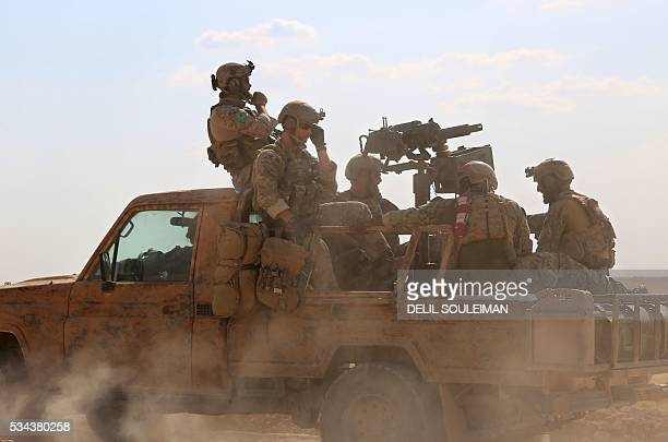 TOPSHOT Armed men in uniform identified by Syrian Democratic forces as US special operations forces ride in the back of a pickup truck in the village...