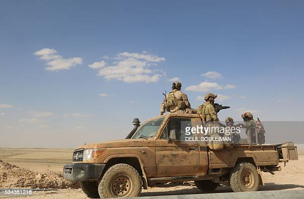 Armed men in uniform identified by Syrian Democratic forces as US special operations forces ride in the back of a pickup truck in the village of...