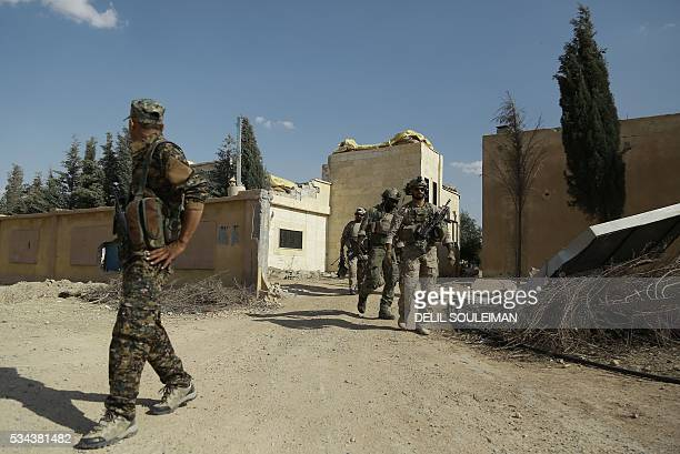 Armed men in uniform identified by Syrian Democratic forces as US special operations forces walk in the village of Fatisah in the northern Syrian...