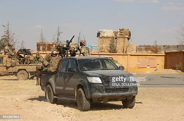 Armed men in uniform identified by Syrian Democratic forces as US special operations forces ride in the back of pickup trucks in the village of...