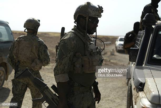 Armed men in uniform identified by Syrian Democratic forces as US special operations forces are seen in the village of Fatisah in the northern Syrian...